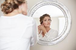 Bride looks in silver mirror