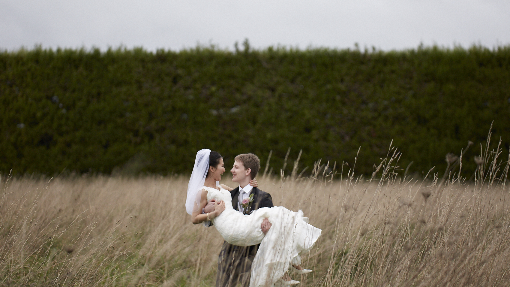 groom carries bride in field