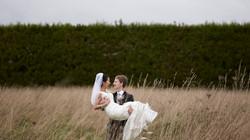groom carries bride in field