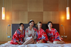 posing bride and bridesmaids on bed