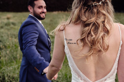 Groom leads bride into field
