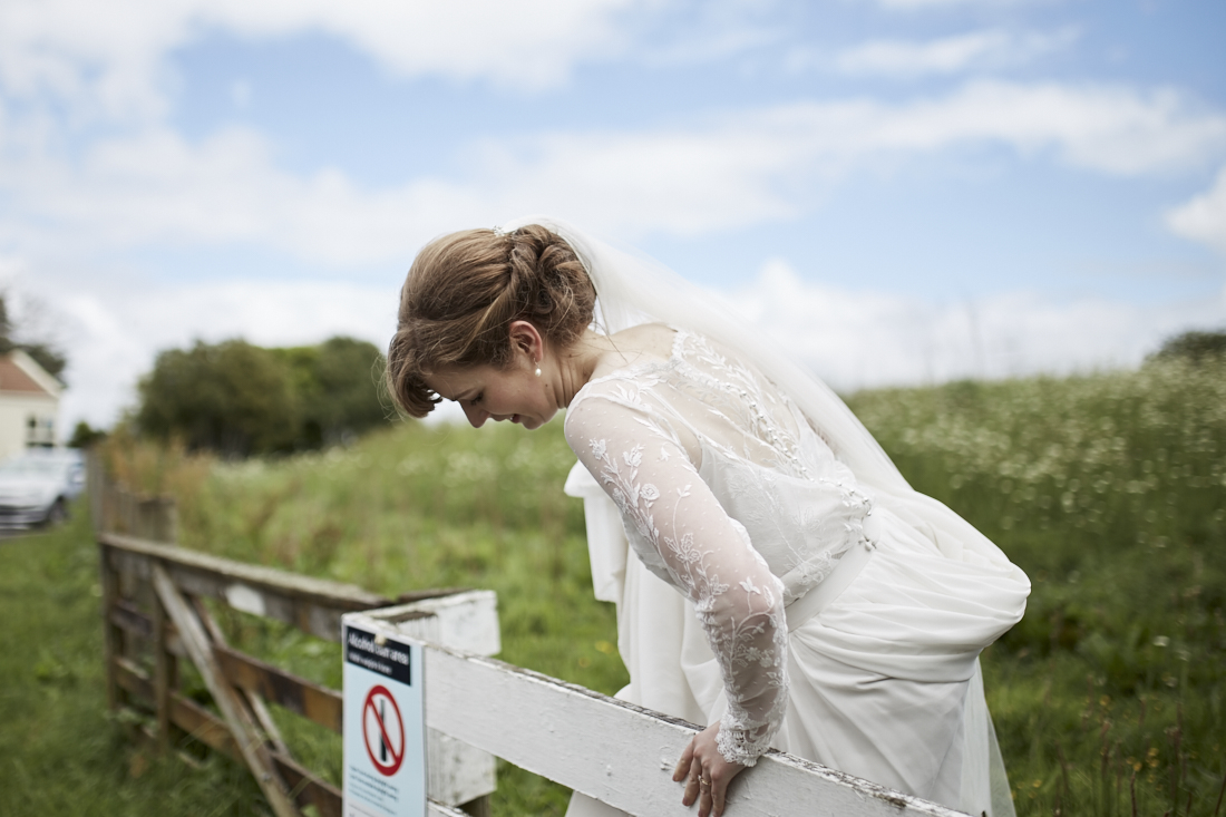 bride climbing fence