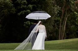 newlyweds with umbrella