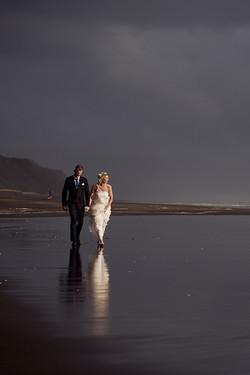 newlyweds strolling along beach