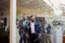 Grooms walking through confetti