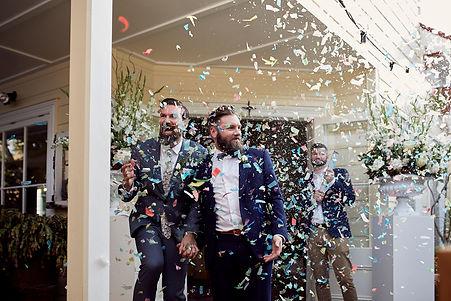 Grooms walking through confetti
