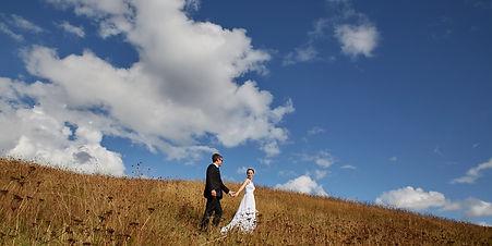 Wedding couple walking through a field