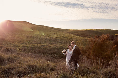 newlyweds walking through a field