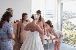 Bride putting on her dress