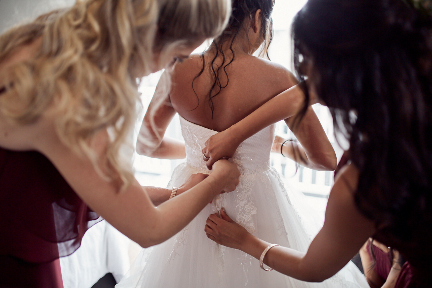 Bride gets dressed by bridesmaids