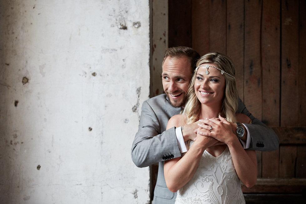 Groom embracing bride