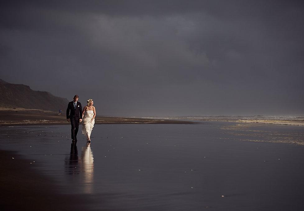 Newlyweds walking along beach