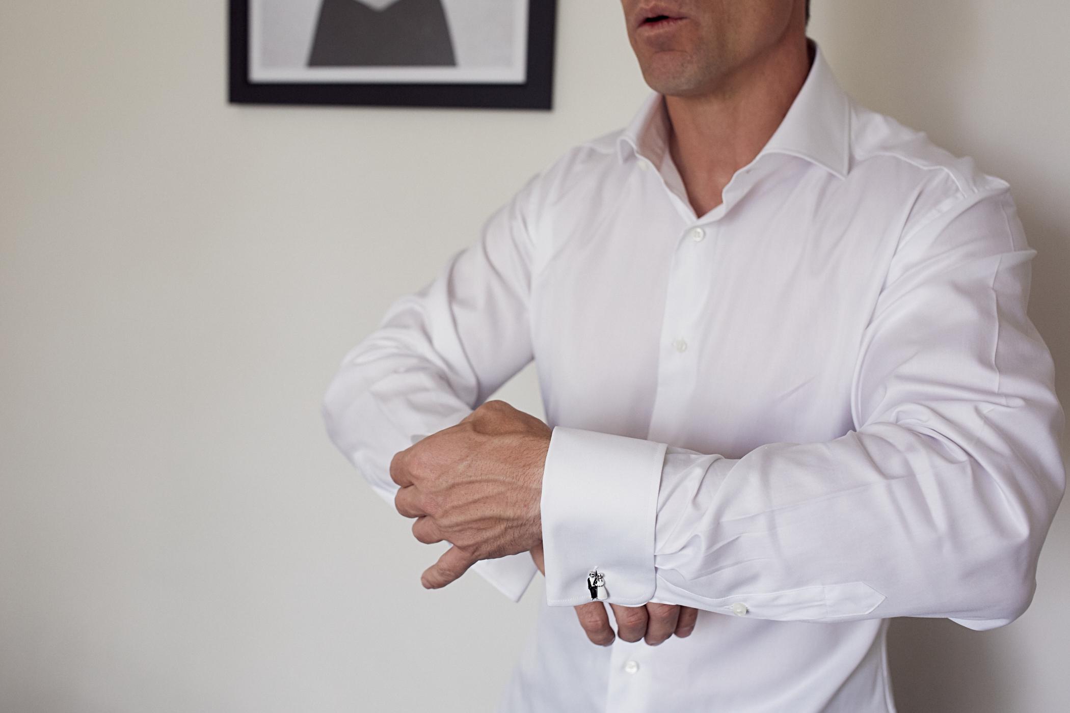 groom adjusts cufflinks