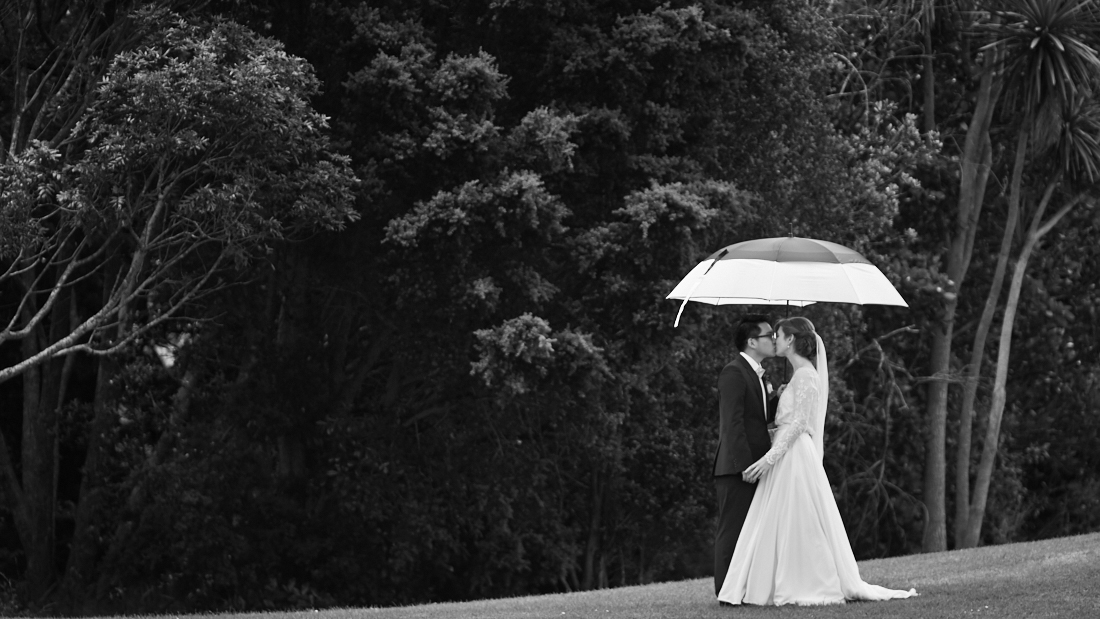 newlyweds under umbrella