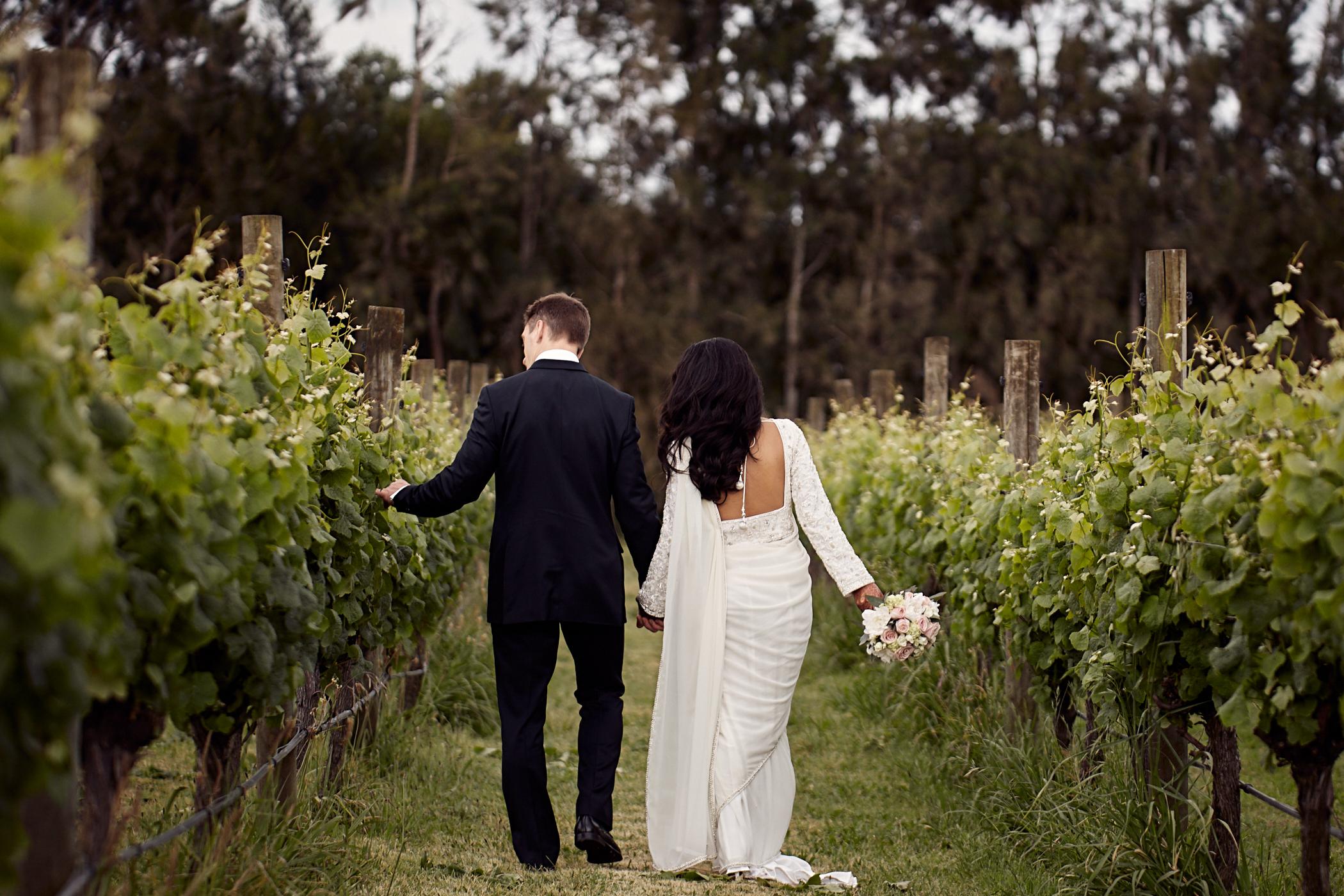 couple walking through vines
