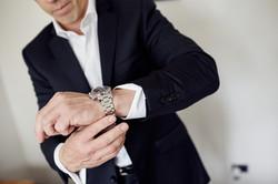 groom adjusts watch