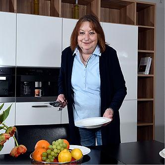 Küchenspezialistin Reni Riedel bei Tisch decken.