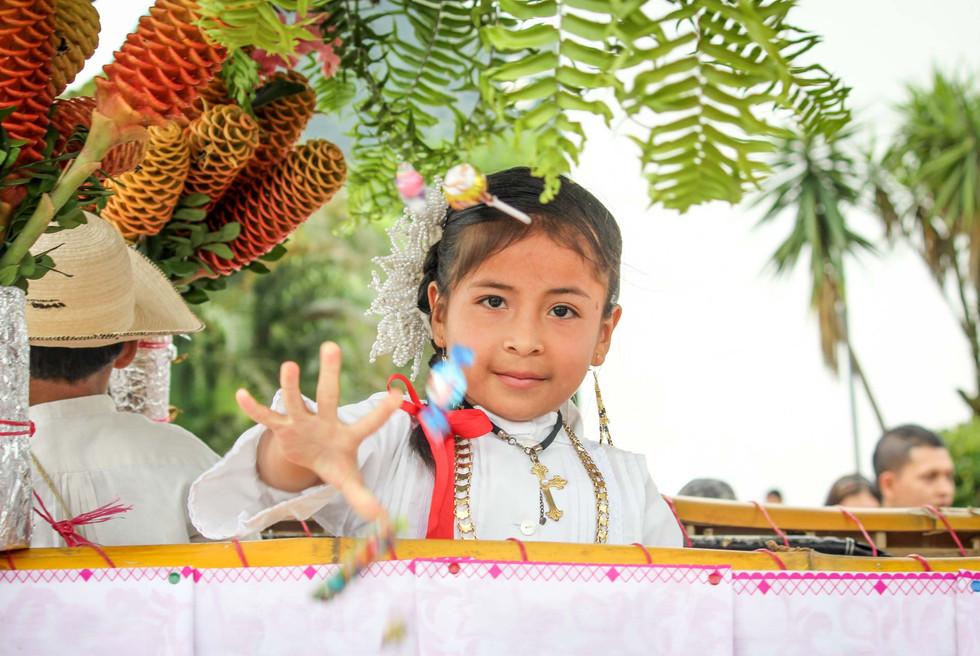 Ein Mädchen verteilt von einem Wagen aus Süßigkeiten