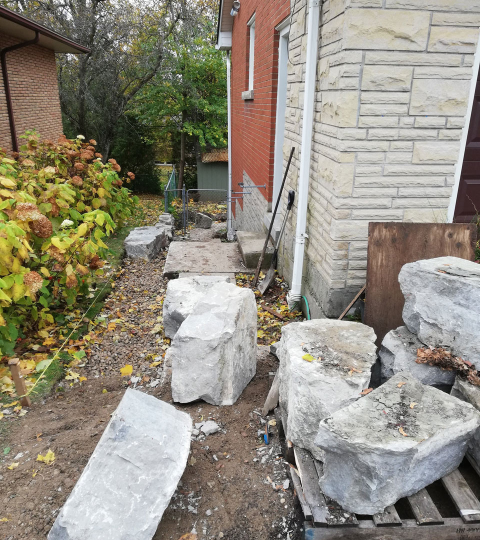 Side yard hardscaping with large stone for retaining wall. Paver stones being remove for walkway to backyard.