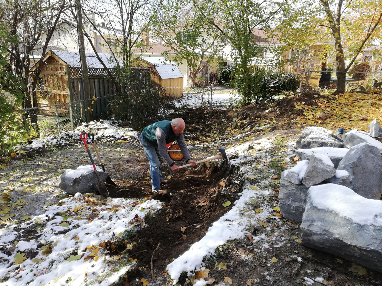 Martin uses a pickaxe to prepare level area for armour stone retaining wall.