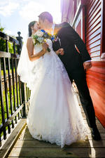 backlit groom kissing bride