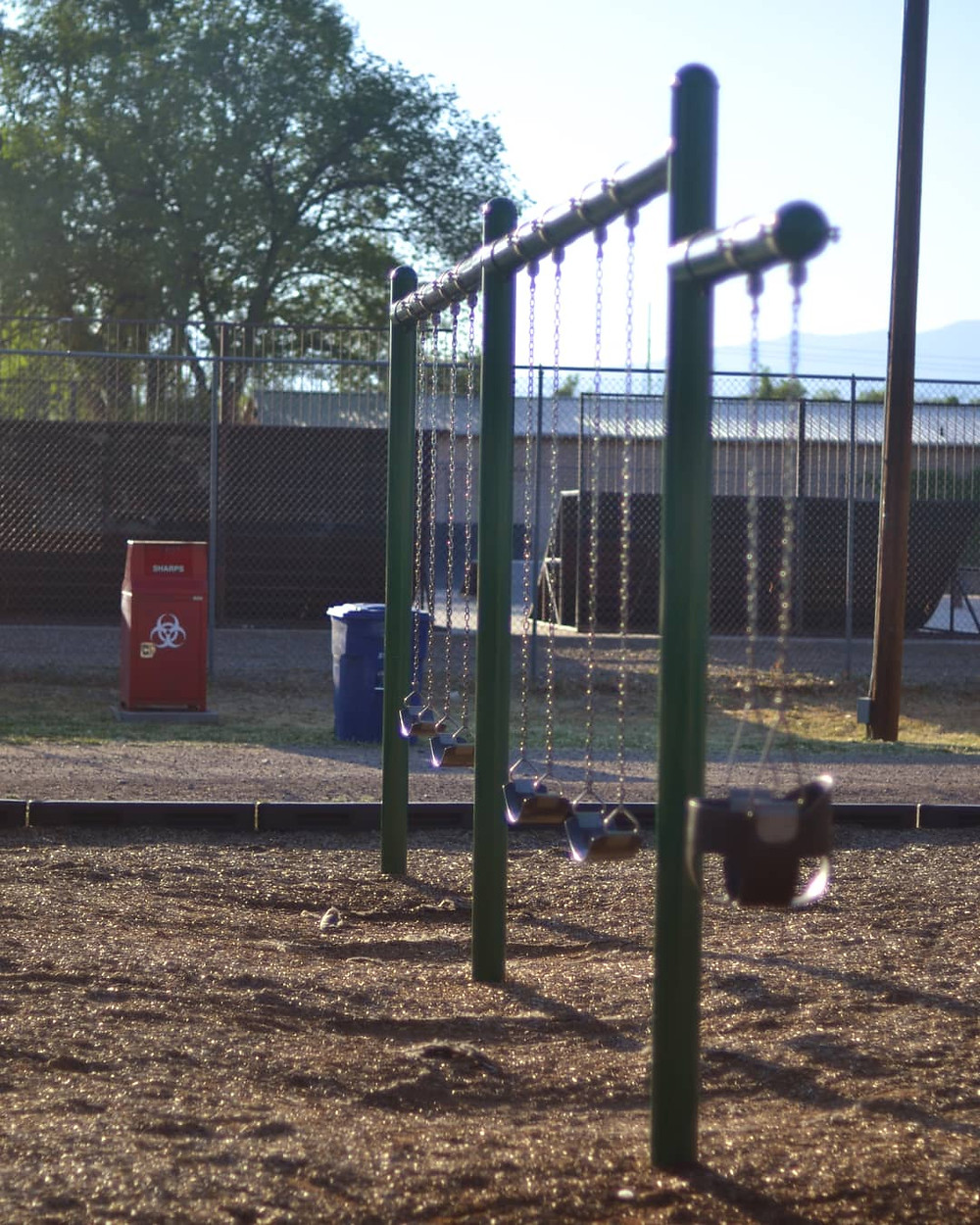 Where Worlds Collide - Sharps container on a playground in Espanola