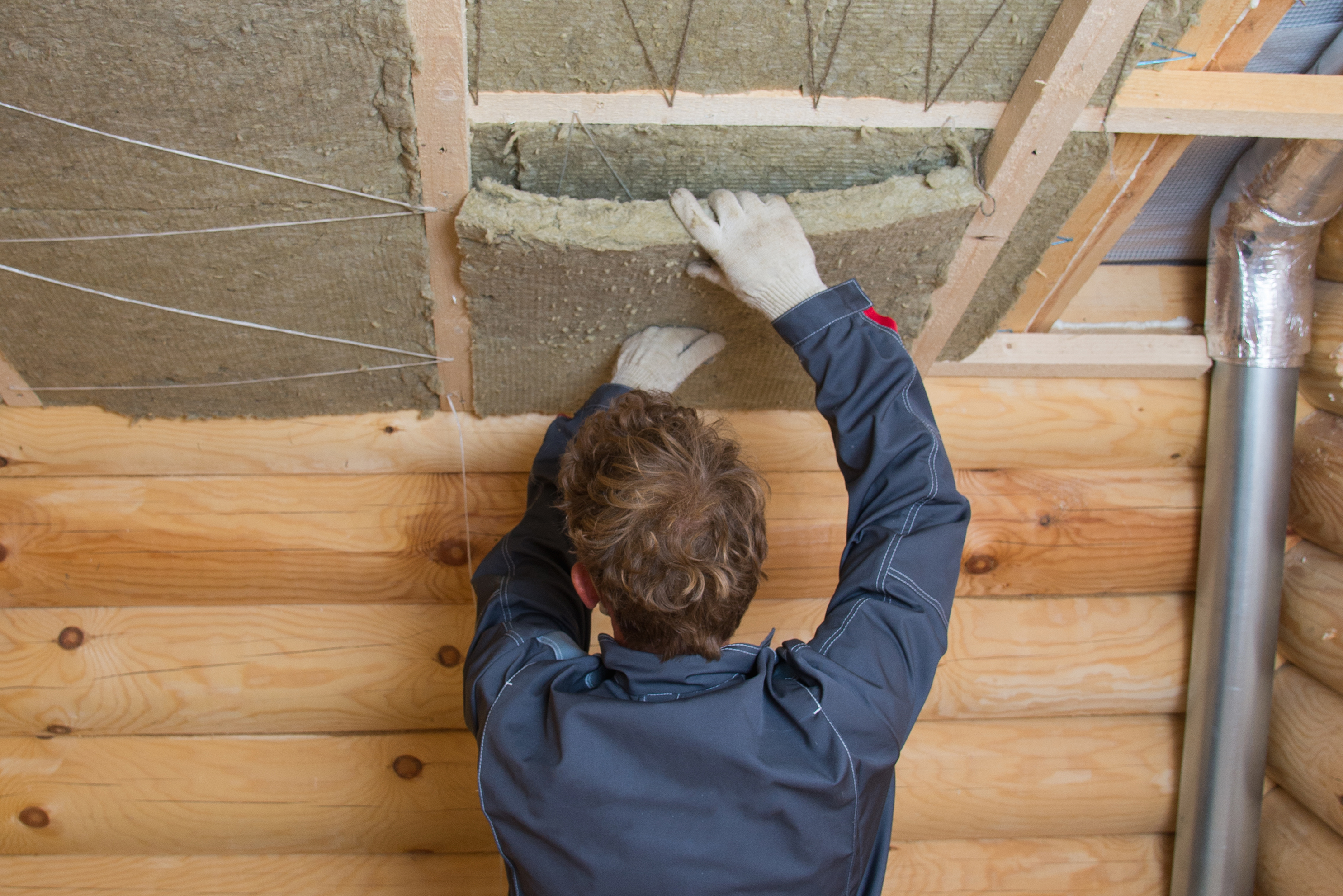 Worker installing insulation panels of mineral wool into roof of house