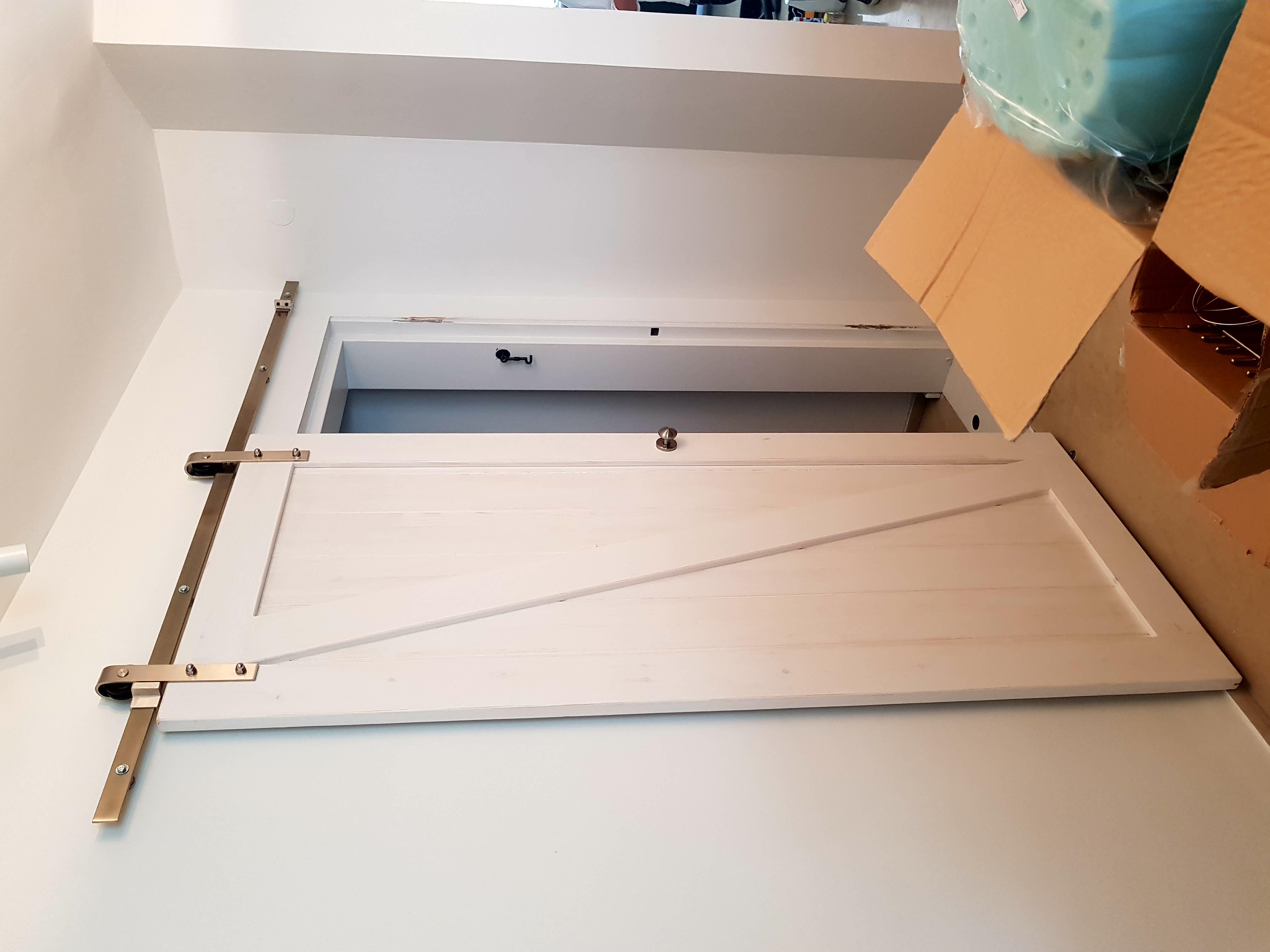 דלת אסם לבנה בשילוב מסילה גלויה בגימור ניקל מוברש