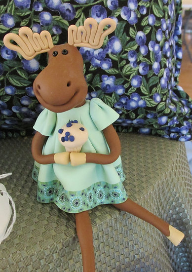 Clay Moose holding a blueberry muffin