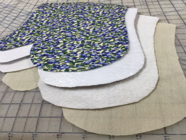 Starting at the top is the fabric layer, followed by Insul Brite ( a heat resistant foil with batting on each side). The third layer is a Warm & White batting ( this batting will absorb any moisture) and the last layer is the lining fabric.