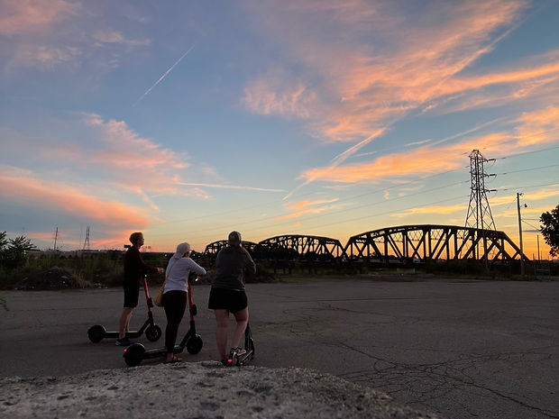 HQ | DYT and CMHx founders standing on scooters looking at sunset by the river and train tracks