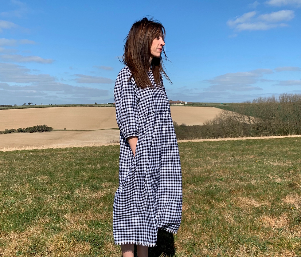 Model wears gingham dress with pockets in a rual countryside setting
