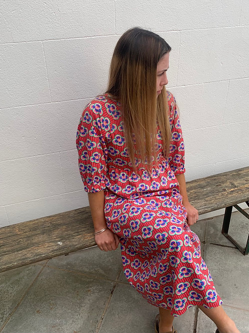 Girl sitting on a bench wearing a red print long dress
