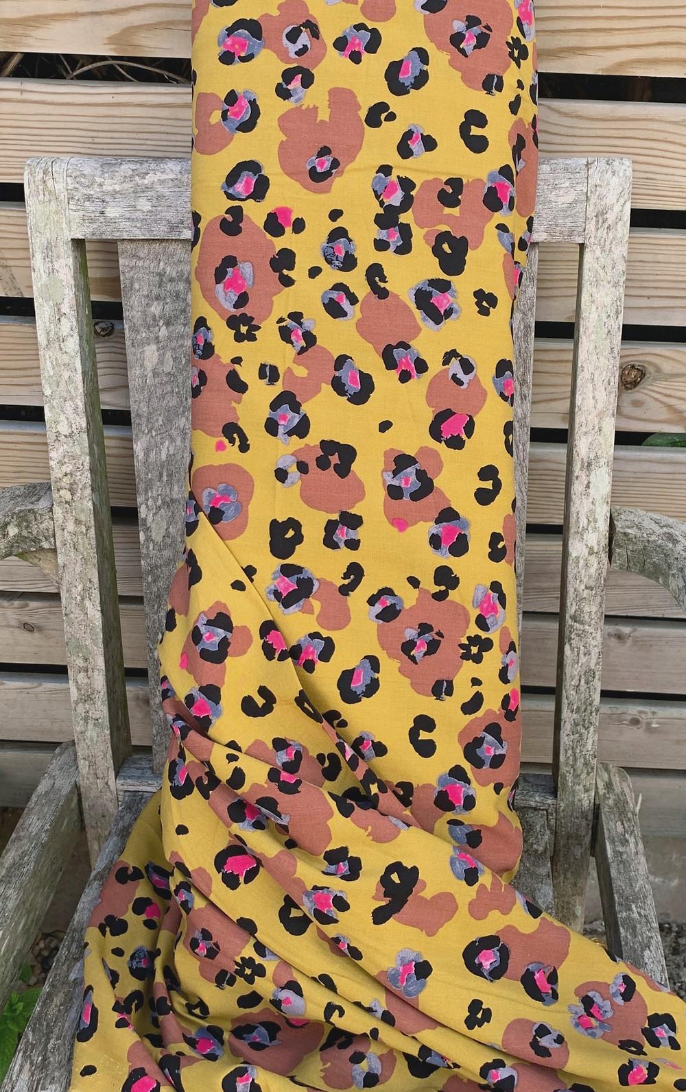 a bolt of fabric in ochre leopard print viscose