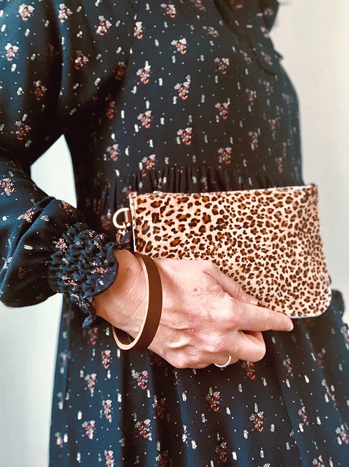 model wearing dress holding animal print leather clutch
