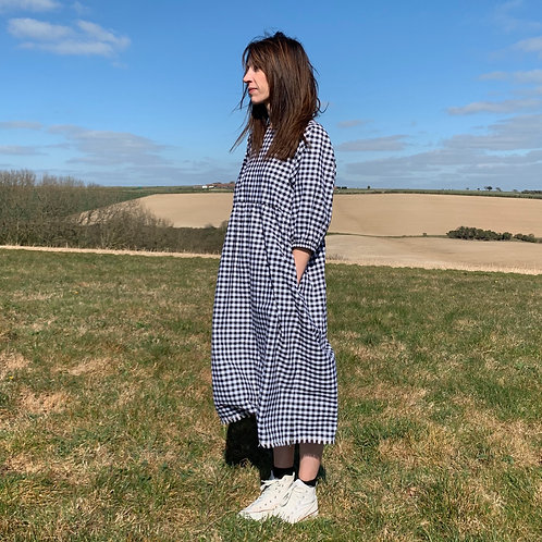 model wearing gingham dress in a rural setting