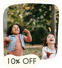 Duas crianças brincando de jogar folhas para o alto em meio a natureza. A imagem também tem uma forma orgânica que tem escrito 10% de desconto para o dia das crianças na Urikana Boutique e Hotel