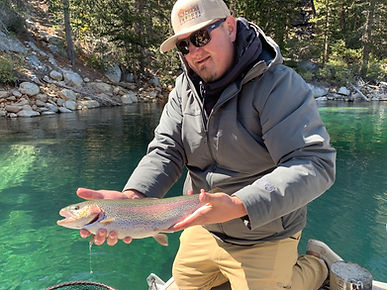 Fisherman holding a large rainbow trout caught on a sierra slammers mini jig