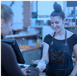 Uma mulher vestindo um uniforme profissional, atrás de um balcão como caixa de loja, recebendo pagamento de uma cliente. Link do curso Qualidade no Atendimento e Postura Profissional do Senai