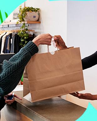 Uma pessoa entregando a outra uma sacola de papelão, em cima de um balcão em uma loja de roupas. Link do curso de Atendimento ao Cliente, do Sebrae