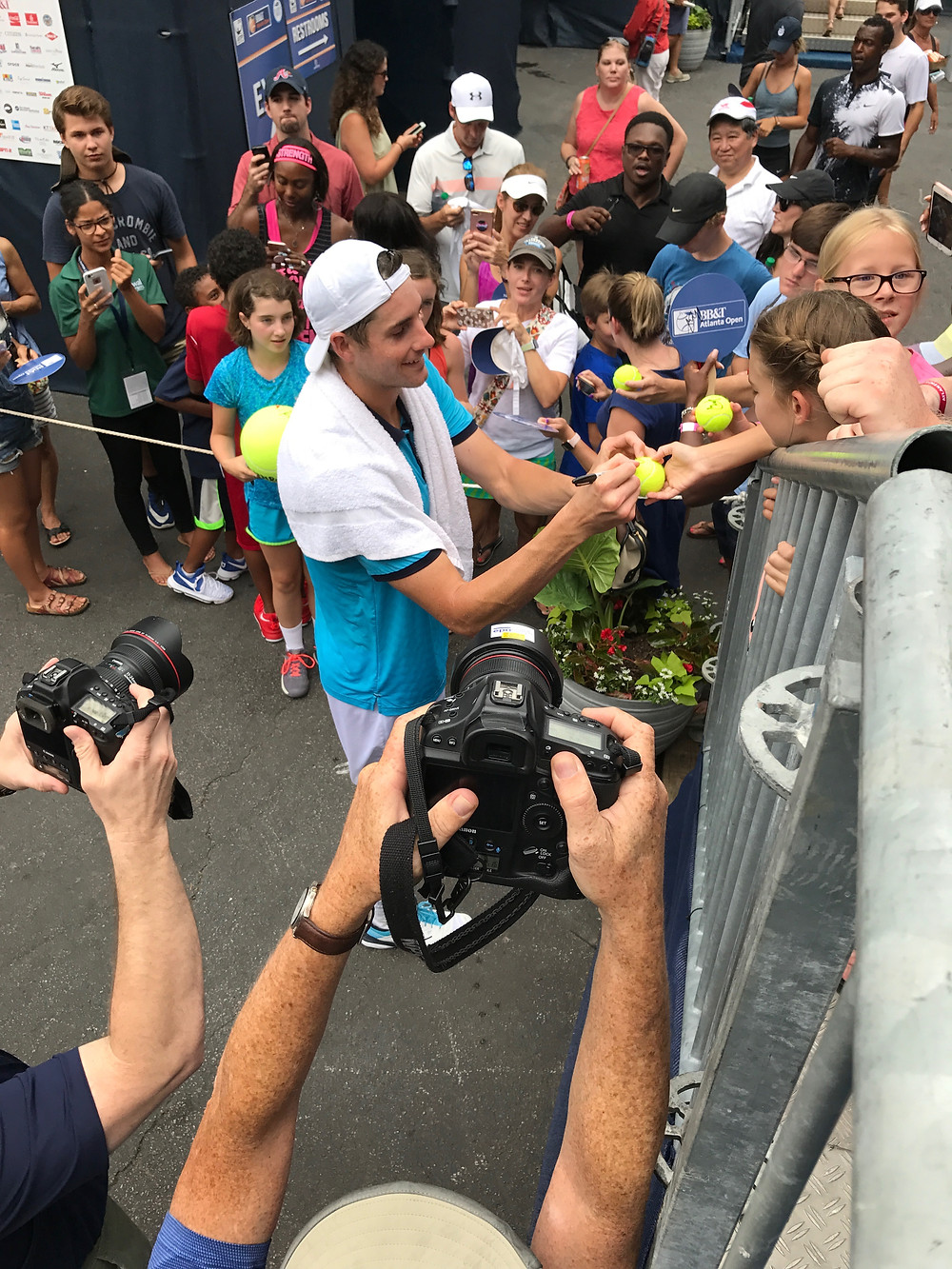 John Isner signing tennis balls after a win at the BB&T Atlanta Open