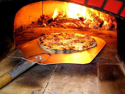 Pečení pizzy v peci na dřevo