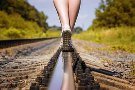 female legs in sneakers on the rail of t