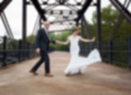 Bride and groom dancing on a bridge, twirling