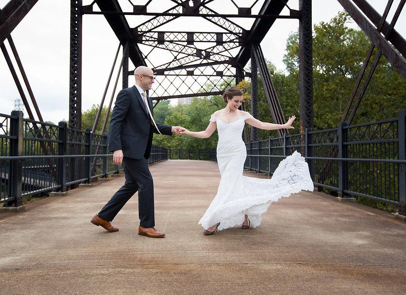 Bride and groom dancing on a bridge, twirling