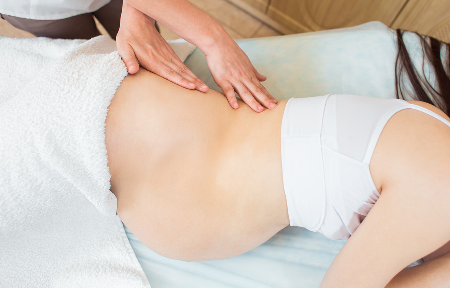 Pregnant woman receiving a massage on a