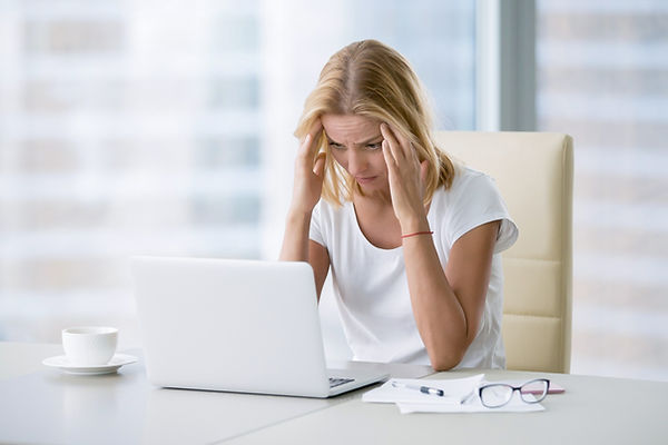 woman working on the computer with a headache
