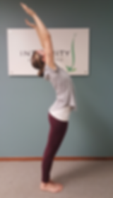 Person leaning backwards with arm overhead.