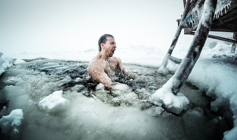 Man swimming in ice hole