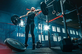 Fit young woman lifting barbells working